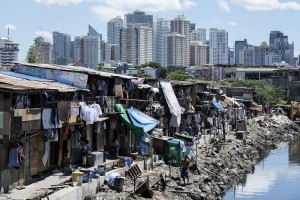 TOPSHOT - People living in a settlement walk about, as the skyline of Manila's financial district is seen in the background, on August 17, 2017.  The Philippine economy grew by 6.5 percent in the three months to June, likely one of the fastest in Asia, the government said on August 17, defying concerns over President Rodrigo Duterte's unconventional leadership. / AFP PHOTO / Noel CELIS        (Photo credit should read NOEL CELIS/AFP/Getty Images)